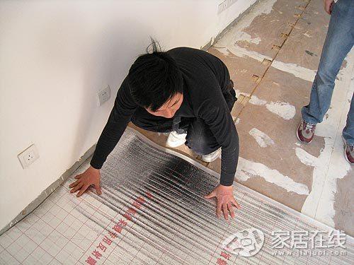 全过程 电热膜/根据画出来的部位用切割机开槽,而另一位工人则拿着扫把和吸尘...